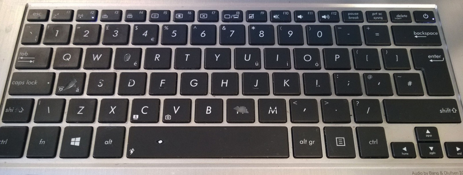 a laptop keyboard showing signs of wear from long term use - patina